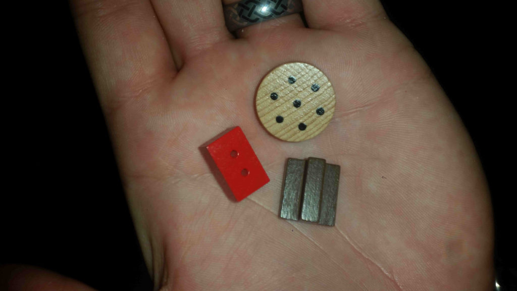 Brick (with tiny little drilled holes), hardtack (food) and wood resource tokens.
